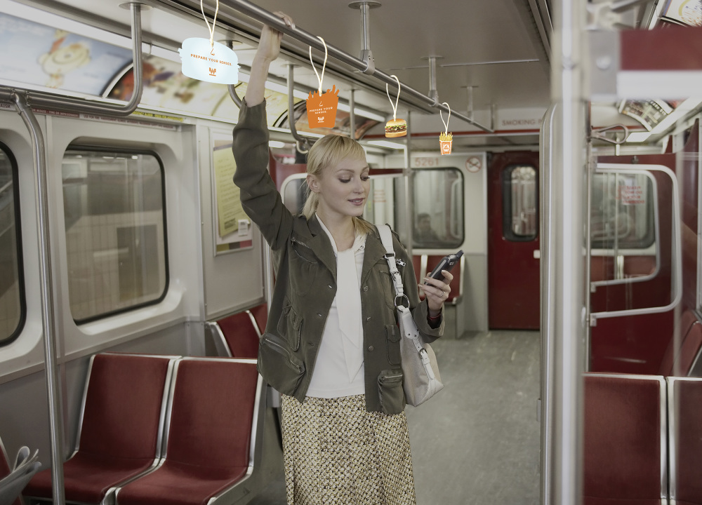 Young woman in empty subway train, holding onto railings, using mobile phone